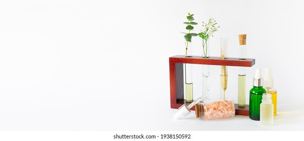 Set of organic skin care products and herbal extracts in test tubes on white background. Face care concept. Eco cosmetic concept. Long banner format.