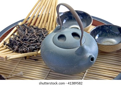 A set of oriental teapot, cups and dry oolong tea on a wooden tray
