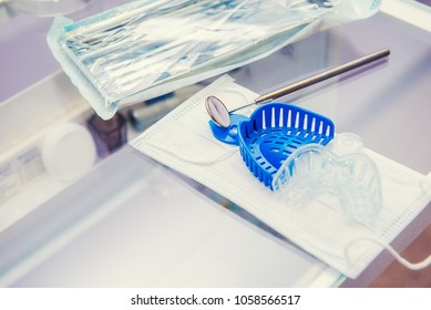 Set of packaged sterilized medical equipment tools, dentist 's mirrow and jaw molds on mask on the working table in orthodontic clinic. Selective focus, space for text.