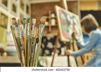 Set of paintbrushes in the foreground and a girl painting a picture on the easel in art studio on the background