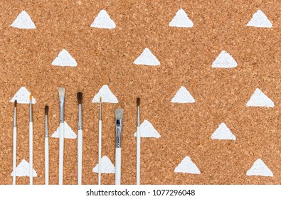 Set of paintbrushes on cork background with white painted triangles. Simple design.