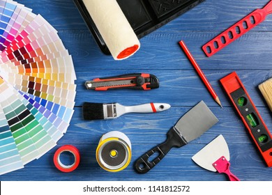 Set of painter's tools on wooden background