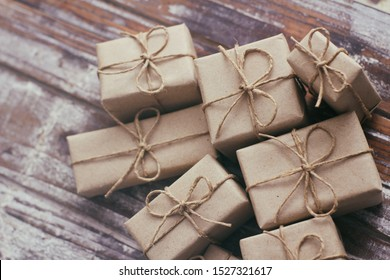 Set of parcel wrapped in craft paper and tie hemp cord. Delivery service. Online shipping. Decorative wooden background. Christmas presents concept. Many gifts.