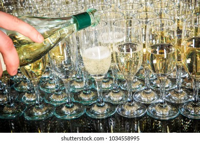 set of partially filled champagne glasses arranged in triangle on mirror background on catering service banquet