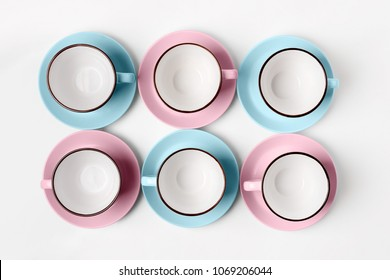 Set of pastel blue and pink porcelain cups arranged in rows on white isolated background, top view