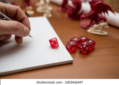 Set of pen, notebook and dices to play role game like dungeons and dragons. Writing with the mechanical pencil on the notebook.