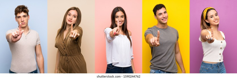 Set of people over colorful background showing and lifting a finger