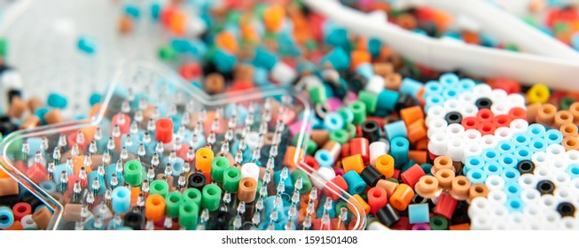 Set of perler beads. Perler pegboard, tweezers and many colorful fusible beads. Toy that develops the imagination of child. Children's toys theme. Wide background with copy space