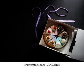 Set of pieces cakes in box on black background.