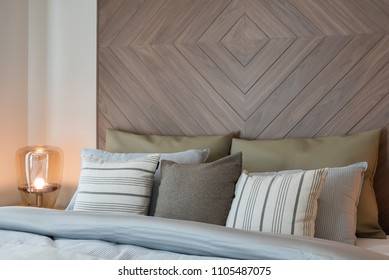set of pillows on bed with wooden wall decoration in classic style bedroom, interior design concept