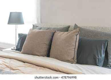 set of pillows on modern bed in bedroom design with lamp