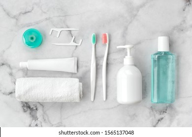 Set of pink and turquoise blue toothbrushes, toothpaste and other tools on marble background. Dental and health care concept. Top view, flat lay.