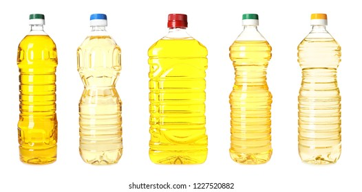 Set with plastic bottles of oil on white background