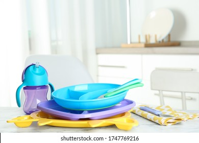 Set of plastic dishware on white marble table indoors. Serving baby food