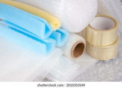 Set of plastic packaging materials - plastic stretch film rolls, foamed polyethylen sheets and rolls, transparent scotch tape, foam edge protectors, small and large bubblewrap rolls. Selective focus - Shutterstock ID 2010353549