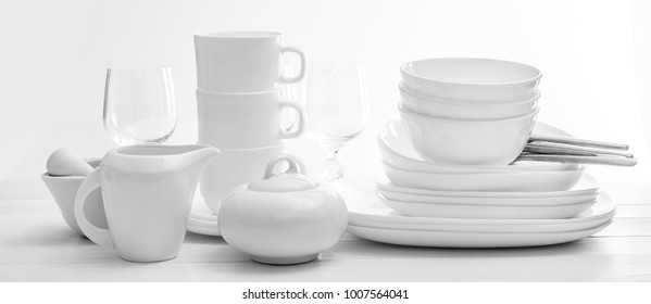 Set of plates and cutleries on light background