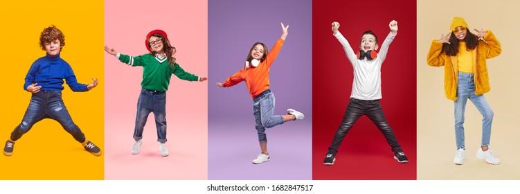 Satz spielerischer, multirassischer, prätenteurer Kinder in trendy, ungezwungener Kleidung, die Spaß beim Stehen auf hellem Hintergrund im Studio