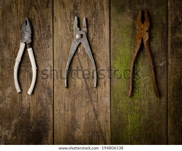 set of pliers on wooden background
