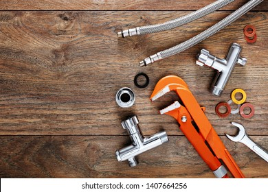 Set of plumbing tools on wooden table background. Close up top down view with copy space.