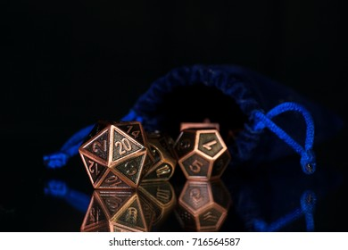 A set of polyhedral dice  with a blue drawstring bag on a mirrored surface. These dice are used for role playing games..