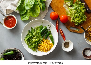 Set of prepared products for the cooking of taco salad on gray concrete background, top view