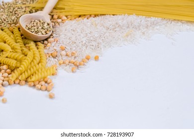 Set of products with complex carbohydrates on white background. wooden spoon, a range of cereals, pasta. Gluten free flour and cereals millet, green buckwheat, basmati rice,up view