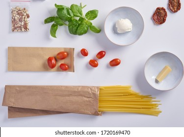 A set of products for an Italian dinner: spaghetti pasta, cherry tomatoes, basil, garlic, cream cheese on a white background. Dinner Set Food Delivery