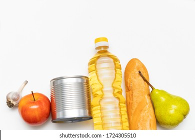 set of products from a loaf of bread, a bottle of vegetable oil, apple, pear, garlic and iron cans of canned food on a white background. place for text.
