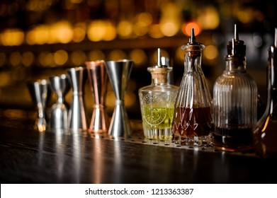 Set of professional barman tools including jiggers and little bottles with liquor and bitters of different colors