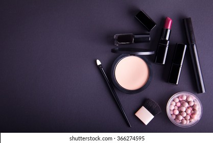 Set of professional cosmetic: make-up brushes, shadows, lipstick, nail polishes on black background. Overhead view. Place for your text. Vignetted.