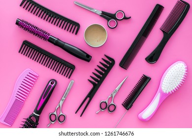 Set of professional hairdresser tools with combs pink background top view