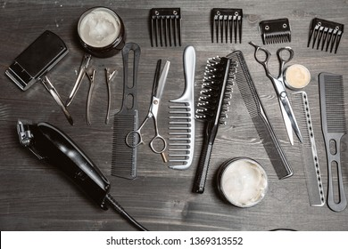 Set of professional hairdresser tools on grey background. Wooden table in barbershop. Working tool of barber master
