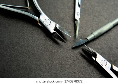 Set of professional tools for manicure master. Nail Cutter, Cuticle Pusher, Cuticle Nipper, Cuticle Scissors on black background with copy space for designe sign. Top view, macro, closeup.