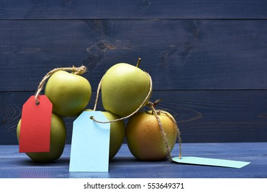 Set of pyramid green fresh apples with colorful tags on blue vintage wooden background, copy space