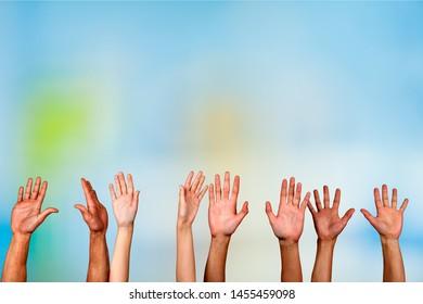 Set of raised hands on blue background