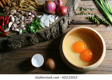 Set of raw egg and Asia ingredients ,garlic,onion,chili,black pepper  on a wooden table.