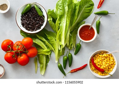 Set of raw food for cooking taco salad on gray concrete background, top view