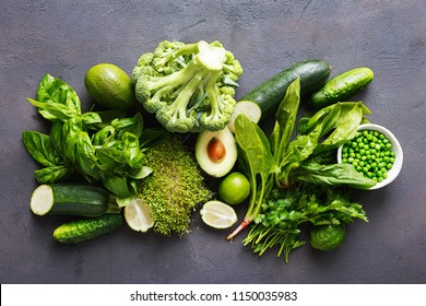 Set raw healthy food clean eating vegetables source of protein for vegetarians: cucumber, lucerne, zucchini, spinach, basil, green peas, avocado, broccoli, lime on black background, top view