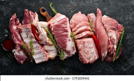 Set of raw meat. Pork meat on black stone background with spices and herbs. Top view. Rustic style.