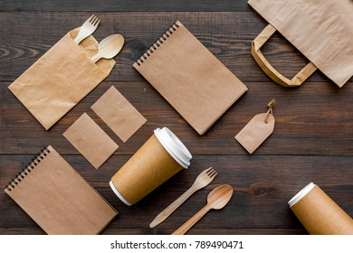 Set of recycle brown paper bag, disposable tableware cup, spoon, fork, notebook on wooden background top view pattern