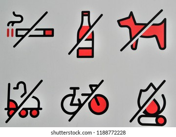 A set of red prohibition signs. No smoking, drinking, biking, no dogs allowed, no skating, no fire. White board with bans