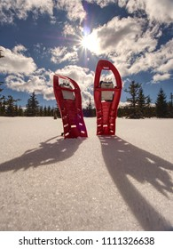 Set of red snowshoes. Snowshoes and a backpack stand on the snow in mountains. Sunny winter day.