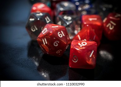 A set of red and transparent RPG dice on a black table