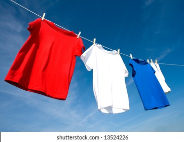 a set of red, white and blue T-shirts hanging on a clothesline on a beautiful, sunny day, add text or graphic to shirts or copy space.  Independance day or USA theme.