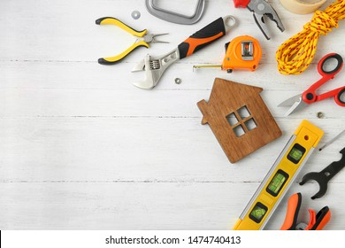 Set of repair tools and house figure on white wooden background, flat lay. Space for text