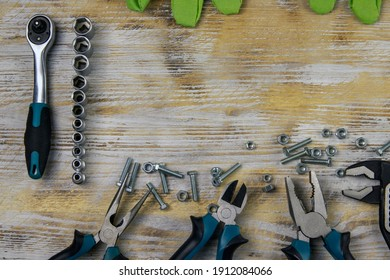 A set of repair tools - screwdrivers, pliers, hardware on a wooden background with a place for text in the center. View from above.