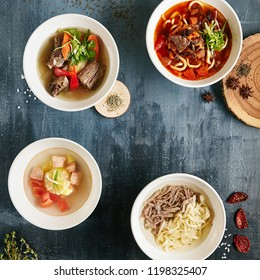 Set of Restaurant Serving Asian Soups on Dark Rustic Background Top View. Kespe Soup, Kullama or Beshbarmak, Fish Soup Bouillabaisse with Salmon, Shurpa, Chorba with Mutton and Lagman