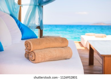 Set of rolled beach towels laying on a white couch in a luxury hotel cabana near the sea