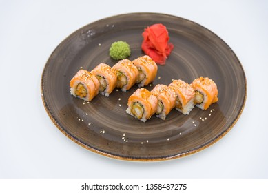 Set rolls with red fish and shrimp on a brown plate close-up.