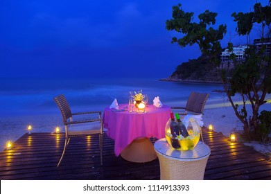 Set up romantic dinner by the sea during the twilight period with a container for chilling a bottle of wine beside the table and light the candles around the area Koh Samui Thailand